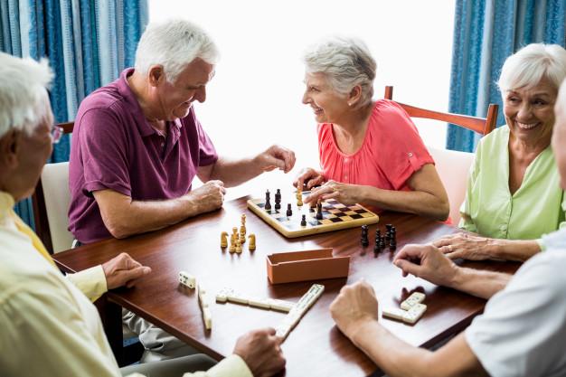 Grupa seniorów gra w szachy - Gminny Ośrodek Pomocy Społecznej w Brzoziu ogłasza nabór uczestników do Klubu Seniora