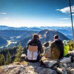 zdjęcia przedstawia dwoje siedzących turystów z plecakami, na szczycie góry